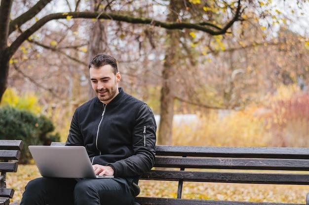 Estudante universitário com computador no parque