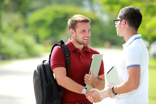 Estudante universitário com mochila feliz em conhecer seu amigo e depois apertar as mãos