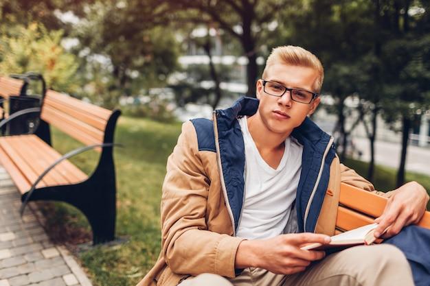 Estudante universitário, com, mochila, livro leitura, andar, em, parque outono, sentar-se banco