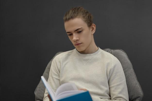 Estudante universitário concentrado, absorto na leitura de algum romance de aventura, sentado na biblioteca da universidade