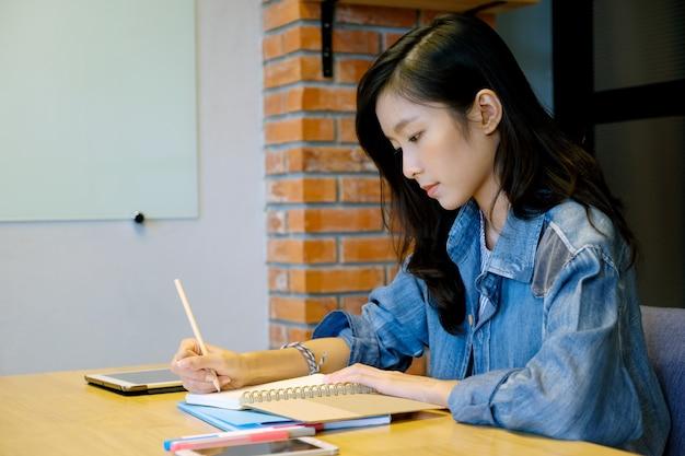 Estudante universitário de mulher asiática na escrita casual no caderno de papel, mão de estudante adolescente escrevendo livro de nota de palestra no campus da escola, faculdade, ensino universitário