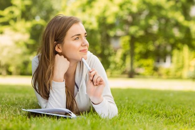 Estudante universitário de sorriso que encontra-se e que pensa