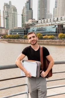 Estudante universitário em uma cidade grande, segurando suas anotações