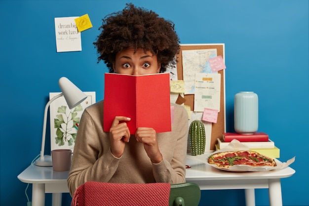 Estudante universitário espantado cobre o rosto com um diário vermelho, chocado por esquecer uma tarefa importante para se preparar