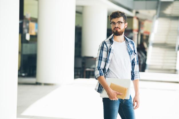Estudante universitário esperando por seu amigo no salão da faculdade