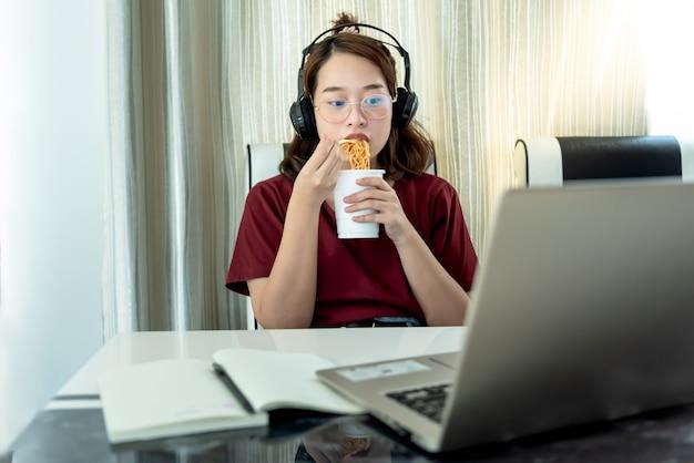 Estudante universitário feminino asiático, comer macarrão copo e assistindo computador notebook