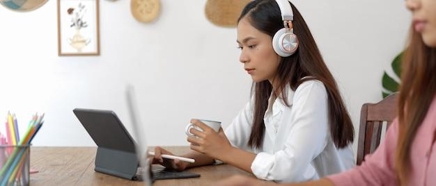 Estudante universitário feminino com aprendizagem on-line de fone de ouvido no tablet digital enquanto está sentado com sua amiga no café