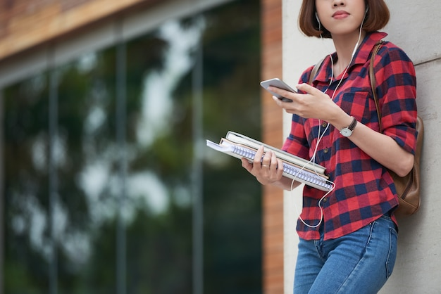 Estudante universitário feminino recortado ouvindo música antes das aulas ao ar livre