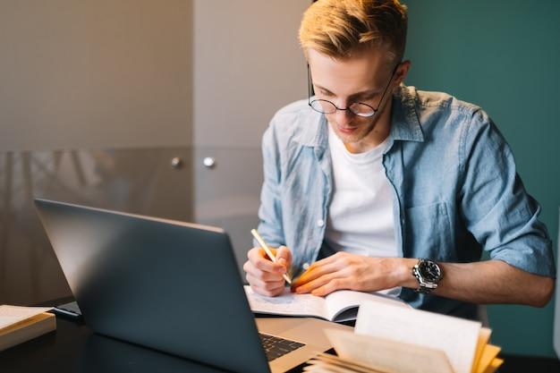 Estudante universitário, homem, caucasiano, usando óculos, estudando com um laptop distante, preparando-se para o exame, escrevendo o ensaio e fazendo a lição de casa em casa