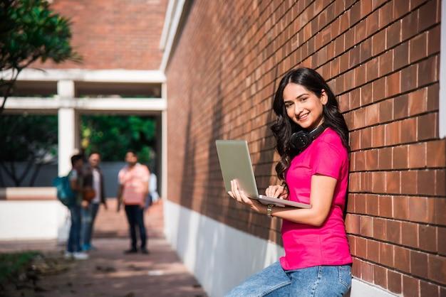 Estudante universitário indiano asiático em foco, trabalhando em um laptop ou lendo um livro enquanto outros colegas de classe ao fundo, uma foto ao ar livre no campus da universidade