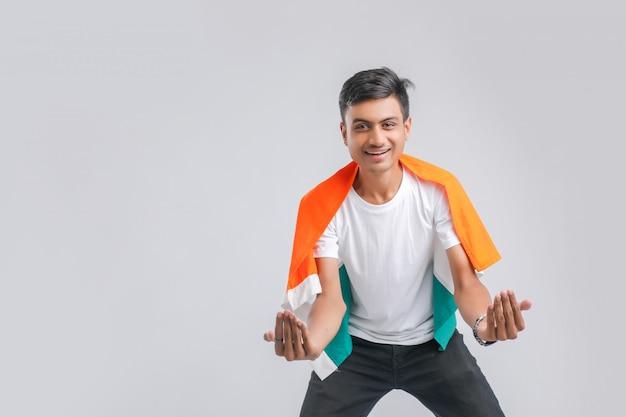 Estudante universitário indiano novo que levanta com bandeira indiana.