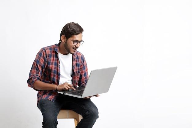 Estudante universitário indiano usando laptop na parede branca