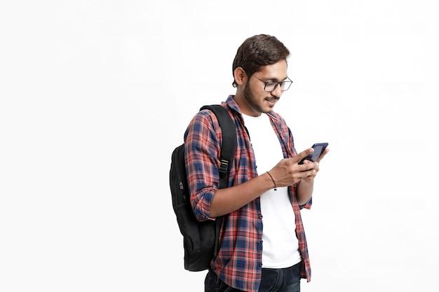Estudante universitário indiano usando smartphone em parede branca