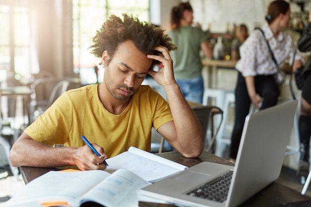 Estudante universitário inteligente em roupas casuais, olhando atentamente em seu caderno escrevendo notas usando o computador laptop, sendo focado em sua escrita sentado no café. homem que trabalha duro estando ocupado