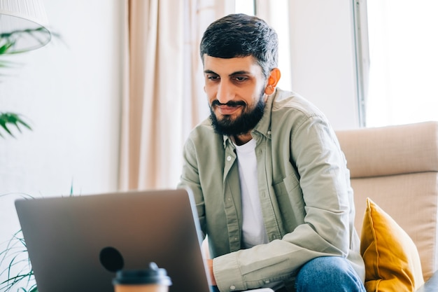Estudante universitário jovem homem caucasiano, estudando com o laptop à distância em casa usando videochamada, tecelagem. conceito de educação à distância.