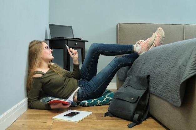 Estudante universitário jovem sentado em casa no chão e estudando usando livros, cadernos. garota esperta com óculos, educação juvenil e autodidata