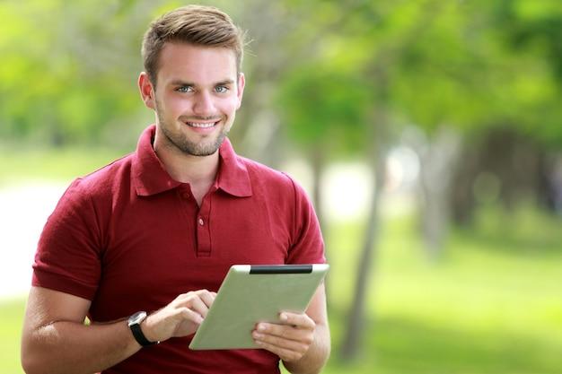 Estudante universitário olhando para a câmera enquanto segura um tablet com espaço de cópia