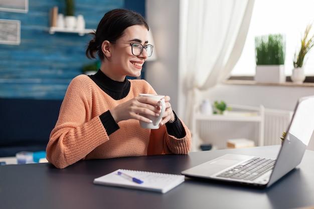 Estudante universitário olhando para o laptop em busca de informações de marketing para o dever de casa. mulher navegando na plataforma da universidade de e-learning na mesa da sala de estar estudando comunicação on-line pela internet