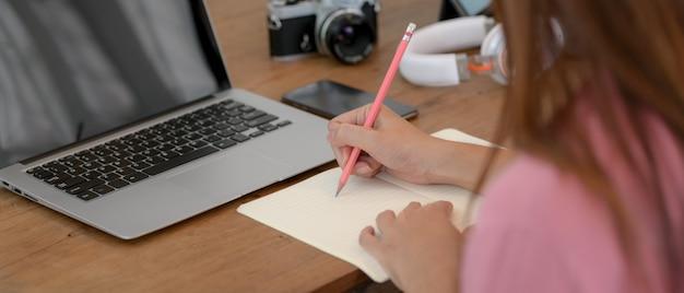 Estudante universitário on-line estudando com laptop e anotando no caderno em branco na mesa de madeira