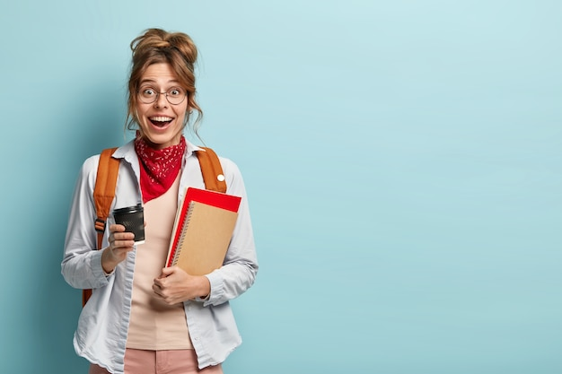 Estudante universitário otimista ri alegremente, segura café para viagem e caderno espiral, faz intervalo após as aulas