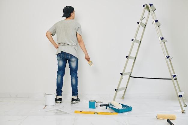 Estudante universitário pintando paredes