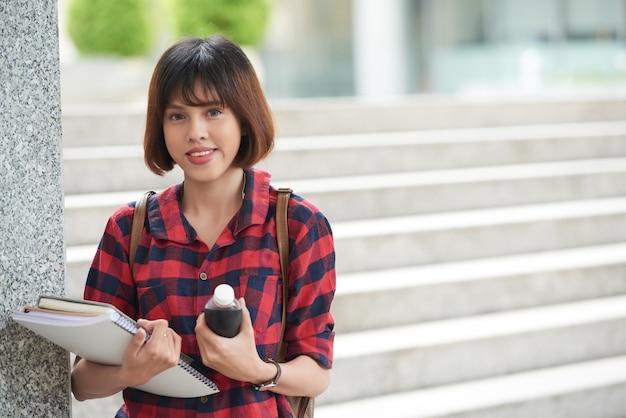 Estudante universitário segurando livros didáticos em pé nas escadas da faculdade, olhando para a câmera