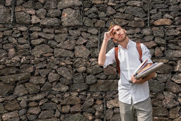 Estudante universitário, segurando pastas de livros e notas e olhando para cima