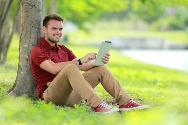Estudante universitário sentado sob uma árvore enquanto joga um tablet com espaço de cópia