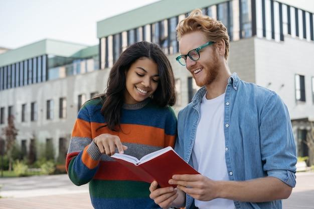 Estudante universitário sorridente lendo livro e estudando preparação para o exame