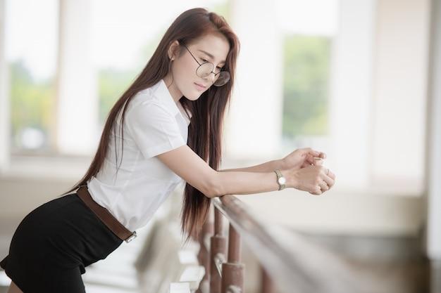 Estudante universitário tailandesa bonita que veste o uniforme tailandês da estudante universitário.