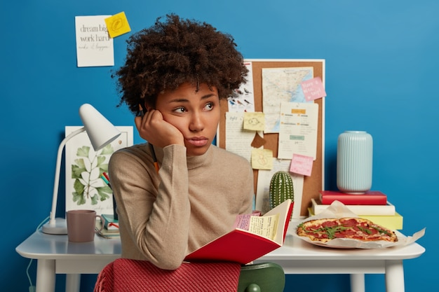 Estudante universitário triste e pensativo segurando um caderno com notas adesivas coloridas dentro