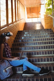 Estudante usando fone de ouvido de realidade virtual e laptop na escada