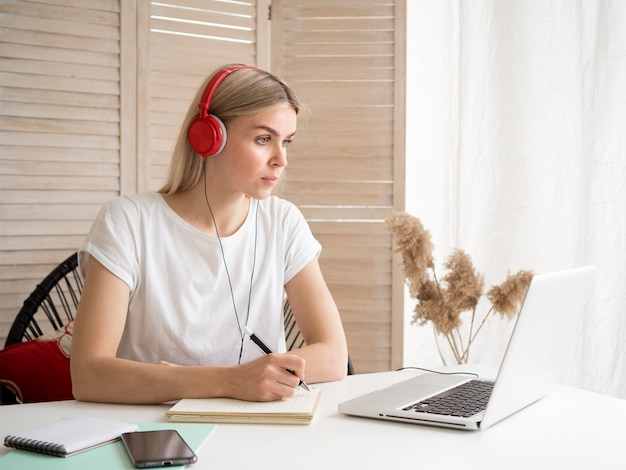 Estudante usando fones de ouvido vermelhos cursos on-line