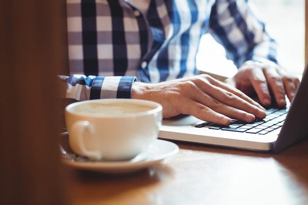 Estudante usando laptop enquanto tomando café