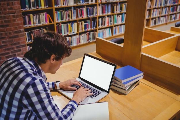 Estudante usando laptop na biblioteca