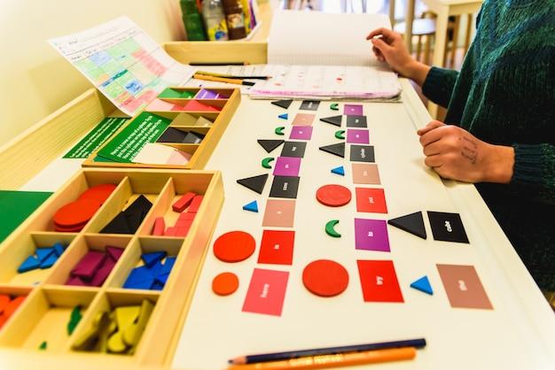 Estudante usando material para aprender formas geométricas em uma escola montessori.
