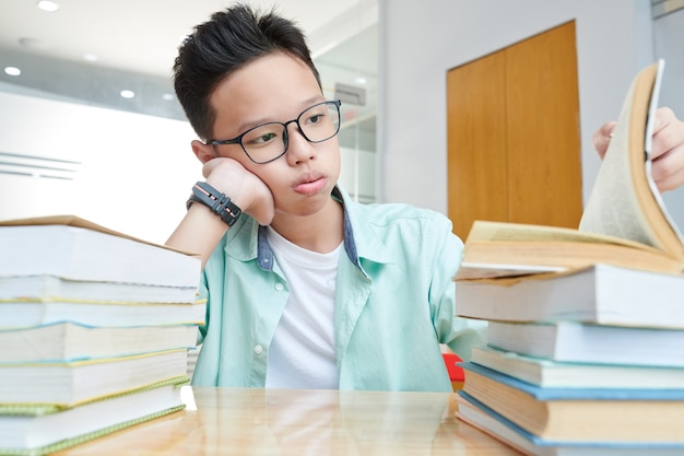 Estudante vietnamita cansado olhando para pilhas de livros em sua mesa que precisa ler para se preparar para o exame