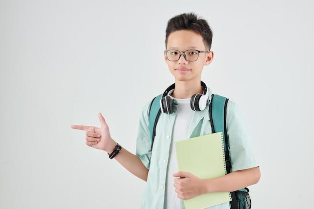 Estudante vietnamita com mochila e livro apontando para longe com o dedo indicador