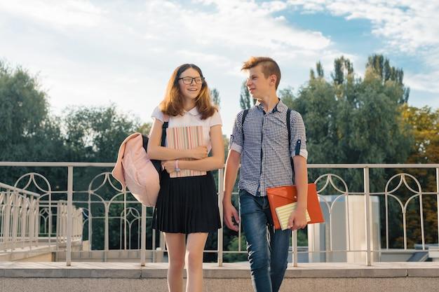 Estudantes adolescentes com mochilas, livros escolares, ir à escola