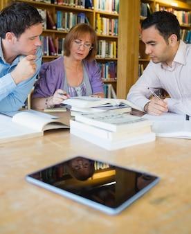 Estudantes adultos estudando juntos na biblioteca