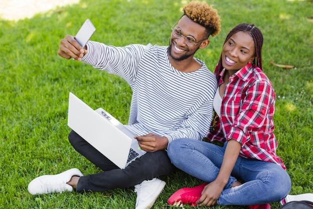 Estudantes alegres levando selfie com laptop