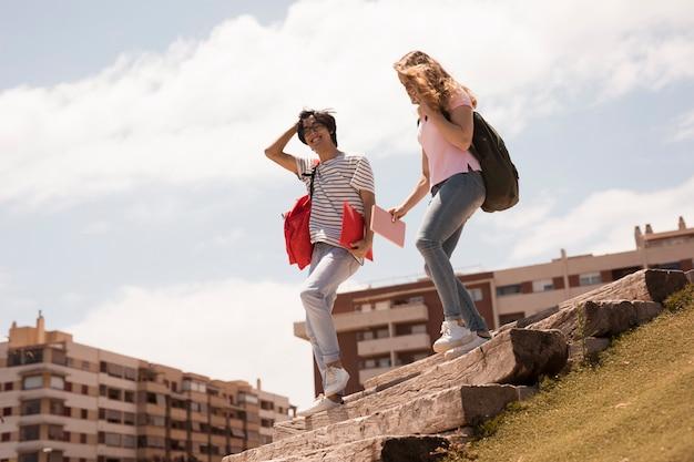 Estudantes alegres multirraciais nas escadas da cidade