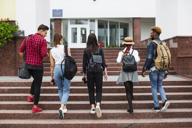 Estudantes anônimos andando pelas escadas