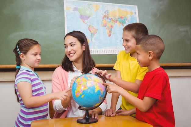 Estudantes apontando para lugares em um globo