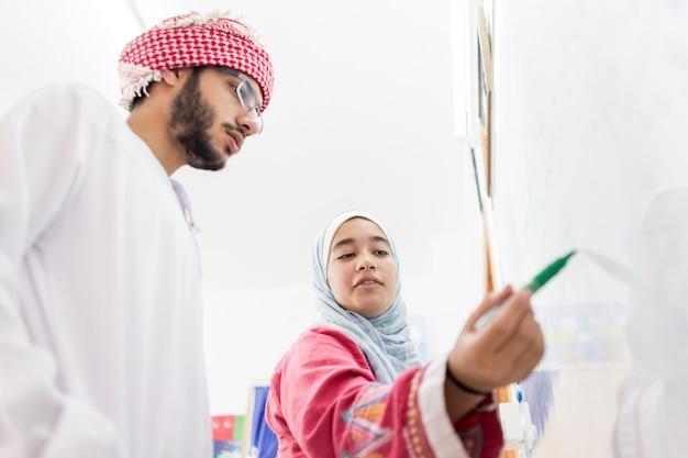 Estudantes árabes muçulmanos, resolvendo uma pergunta de matemática no quadro