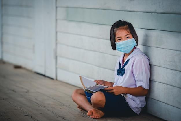 Estudantes asiáticas do ensino fundamental feminino usando uma máscara médica para prevenir o coronavírus