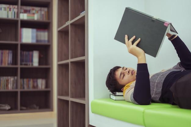Estudantes asiáticos deitam-se lendo livros na biblioteca de lições para o exame do conceito educacional.