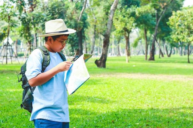 Estudantes asiáticos do sexo masculino carregando uma mochila de viagem, usando um chapéu, segurando um mapa para viajar para aprender