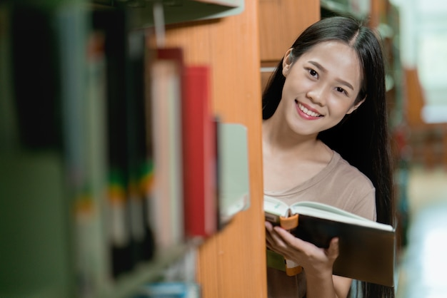 Estudantes asiáticos estão lendo livro na biblioteca