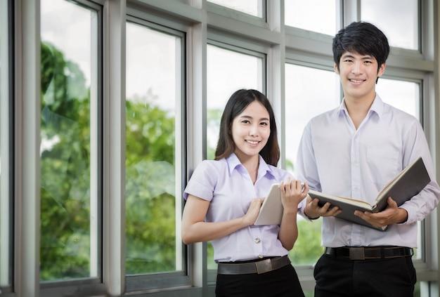 Estudantes asiáticos na universidade lendo um livro
